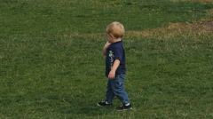 Cute toddler walks backwards in grassy park Stock Footage