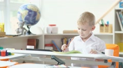 Interior of a child's room. A boy holding a brush to paint Stock Footage