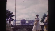 1958: visitors look at and leave historic above-ground tombs enclosed by metal Stock Footage