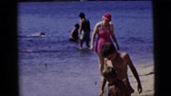 1958: various people walking in the sand and surf on the beach NEW YORK CITY Stock Footage