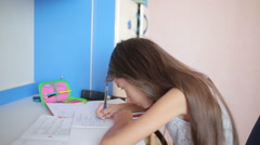 Girl schoolgirl doing homework. Girl learns lessons in the bedroom Arkistovideo