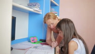 Mom helping her daughter do homework. Girl makes lessons Stock Footage
