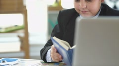 A child in a business suit. The boy is holding a notebook Stock Footage