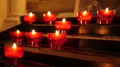 Lot of Catholic prayer red cup votive candles in candle rack  slow motion 108 Stock Footage