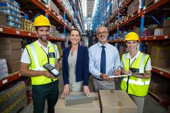 Businessmen and warehouse workers in warehouse Stock Photos