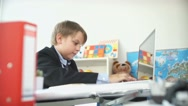 Funny little boy in business suit and sitting at table typing on laptop Stock Footage