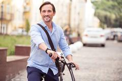 Cheerful man riding a bike Stock Photos