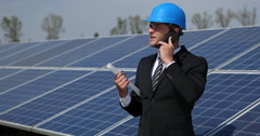 Young Businessperson Talking Cellphone Holding Plans Solar Panels Power Plant Stock Footage