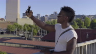 Man Takes Selfies On A Bridge In The City Stock Footage