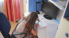 Girl schoolgirl doing homework. Girl learns lessons. using smartphone Arkistovideo