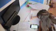 Girl schoolgirl doing homework. Girl learns lessons. using smartphone Stock Footage