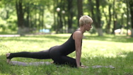 Woman practicing yoga in the park. Stock Footage