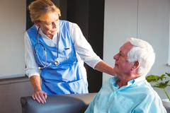 Nurse taking care of a senior man in a retirement home Kuvituskuvat