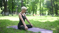 Woman sitting in lotus pose in the park. Stock Footage