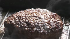 Beef patty preparing on grill pan in 180fps slow motion Stock Footage