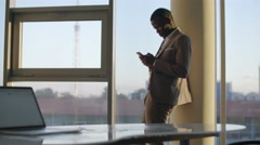 Young black businessman in suit using smartphone standing by window in office in Stock Footage
