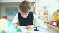 The boy looks at the globe using a magnifying glass Stock Footage