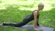 An adult woman doing stretching in a park. Stock Footage