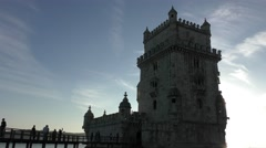 The sun appears behind Torre de Belem Tower in Lisbon, Portugal Stock Footage