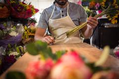 Male florist trimming flower stem at his flower shop Stock Photos