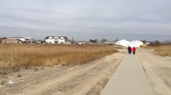 Establishing shot of Breezy Point town from the beach.  A concrete walkway is Stock Footage