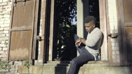Man Sits In A Window In An Urban Brick Building, He Plays With His Smart Watch Stock Footage