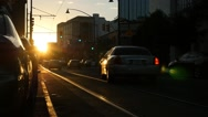Urban sunset with city traffic at a stoplight Stock Footage