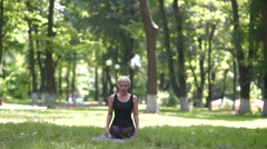 Blonde doing headstand in park. Stock Footage