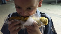 Little boy eating corn on the cob Stock Footage