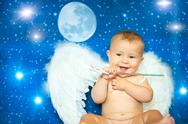 Baby a few months with a magic wand and angel wings Stock Photos