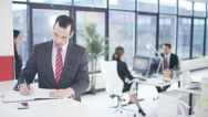 4K Portrait smiling businessman in office with colleagues working in background Stock Footage