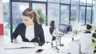 4KPortrait smiling businesswoman in office with colleagues working in background Stock Footage