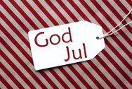 Label On Red Wrapping Paper, God Jul Means Merry Christmas Stock Photos