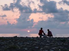 Happy family - father, mother, baby son see sunset sea surf on black sand beach Stock Photos