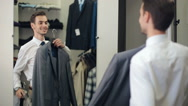 Man choosing a suit at clothing store Stock Footage