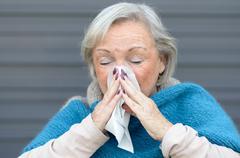 Elderly woman with seasonal influenza Kuvituskuvat