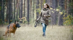 Young woman holding a leash running with a shepherd dog in autumn forest, slow Stock Footage
