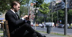 Business Man Working Online with a Digital Tablet Sitting on a Comfortable Bench Stock Footage
