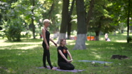 The trainer of yoga helps girls pull her hands. Stock Footage