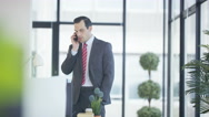 4K Businessman talking on cell phone in modern city office building Stock Footage