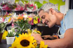 Close-Up of male florist trimming stems of flowers at his flower shop Stock Photos