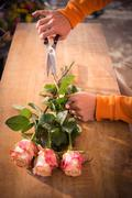 Close-up of male florist trimming flower stem at his flower shop Stock Photos