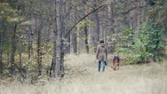 Young woman walking with a shepherd dog in autumn forest goes away Stock Footage