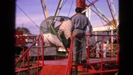 1963: young men enter rock-o-plane ride at amusement park and attendant locks Stock Footage