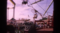 1963: visitors walk through amusement park and enjoy mechanical rides.  Stock Footage