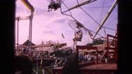 1963: visitors walk through amusement park and enjoy mechanical rides.  Stock Footage