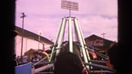 1963: people at a fair on a clear day and kids riding a ride together  Stock Footage
