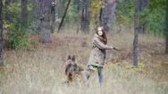 Young woman playing with a shepherd dog in autumn forest - runs for the thrown Stock Footage