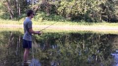 Man in pond reeling in fishing line Stock Footage