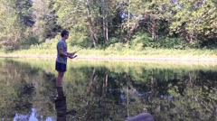 Man standing in pond and reeling in fishing line Stock Footage